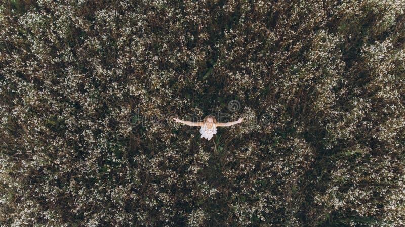 Piękna kobieta z długie włosy w białej smokingowej pozyci w polu z ona ręki up w górze zdjęcie royalty free