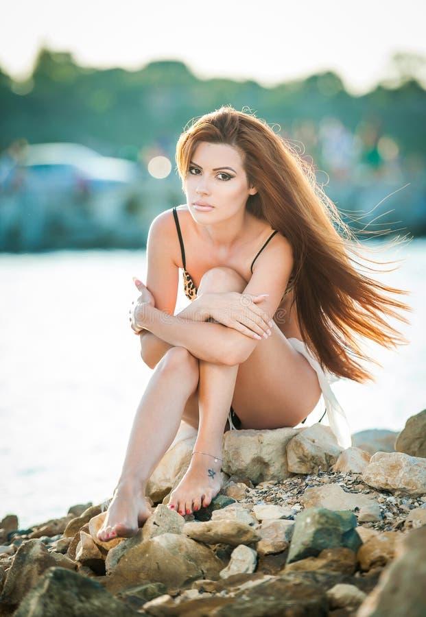 Piękna kobieta z długie włosy w kostiumu kąpielowego obsiadaniu na plaży w letnim dniu Portret szczupła rudzielec w bikini na pla zdjęcia royalty free
