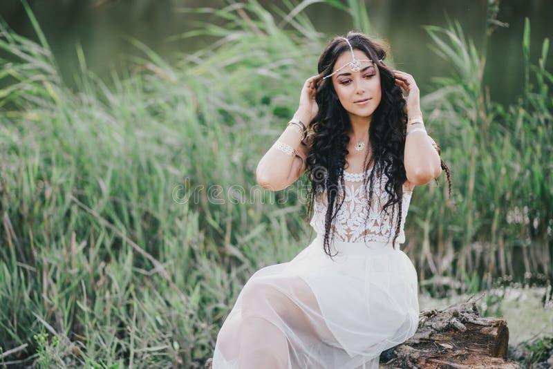 Piękna kobieta z długim kędzierzawym włosy ubierał w boho stylu smokingowy pozować blisko jeziora obrazy stock