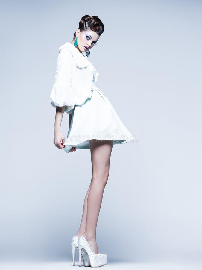 Piękna kobieta z długimi nogami w biel sukni, futerku i szpilkach pozuje w studiu, obrazy royalty free