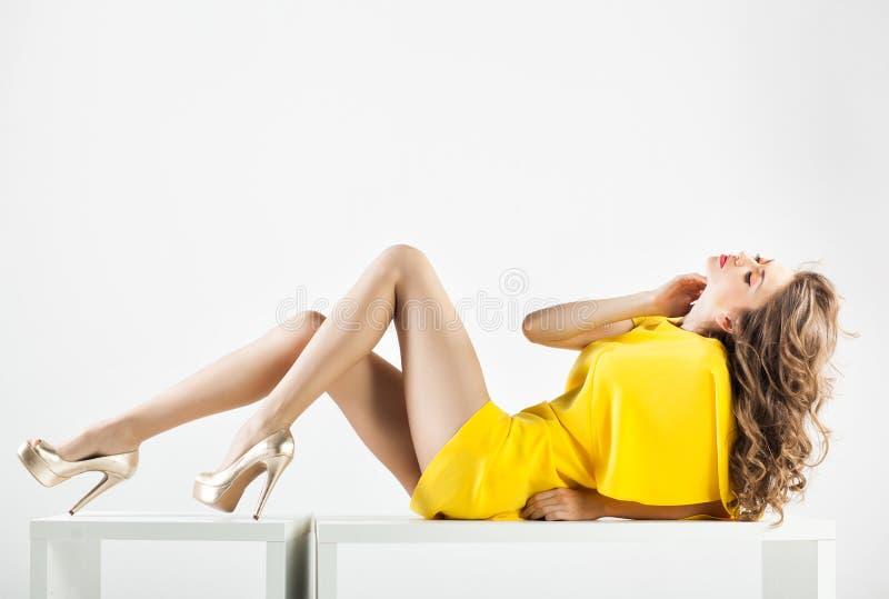Piękna kobieta z długimi seksownymi nogami ubierał elegancki pozować w studiu - folował ciało zdjęcie stock