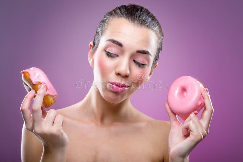Piękna kobieta z dwa donuts Ty możesz jeść lub nie? zdjęcia royalty free