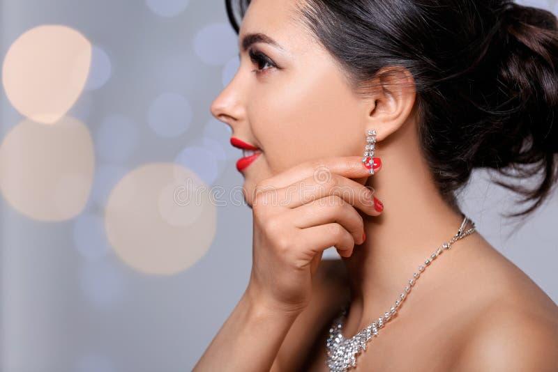 Piękna kobieta z elegancką biżuterią na zamazanym tle, zbliżenie obrazy royalty free