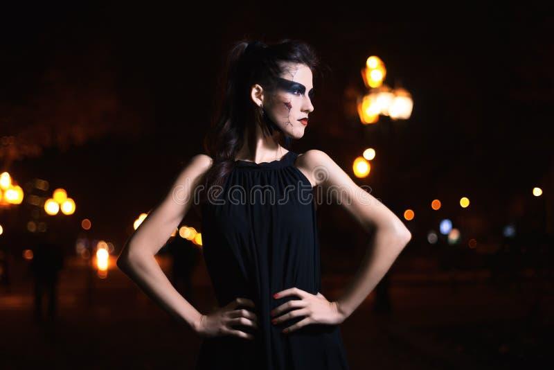 Piękna kobieta z Halloweenowym makeup pozuje na ulicie na boku patrzejący wzorcowy Talia up Nocy miasta tło stonowany fotografia stock