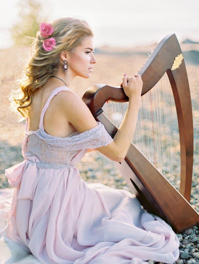 Piękna kobieta z harfą zdjęcie stock