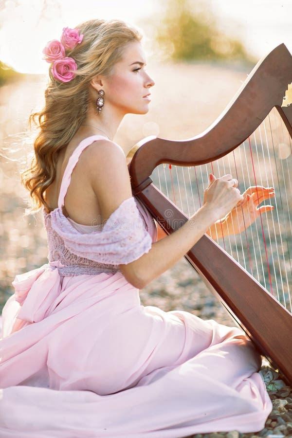 Piękna kobieta z harfą obraz stock
