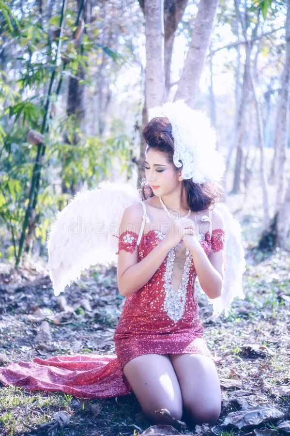 Piękna kobieta z kątów skrzydłami czerwieni sukni obsiadanie w lesie obrazy royalty free