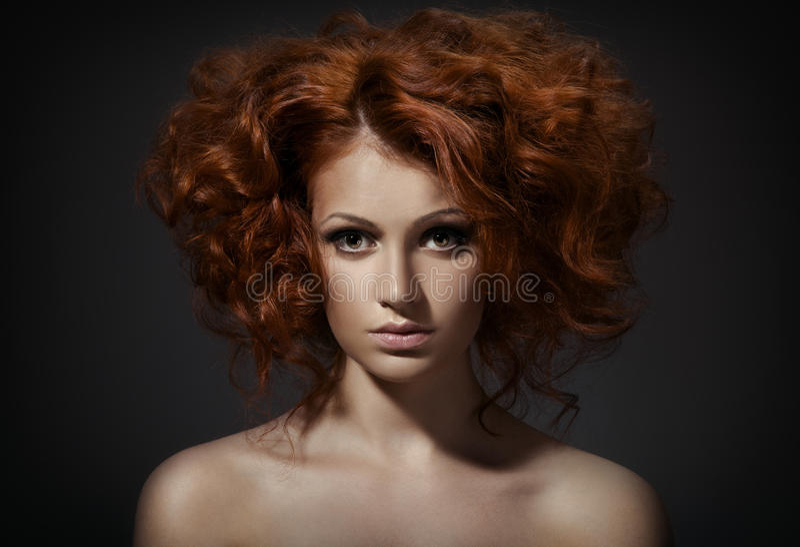 Piękna kobieta z kędzierzawą fryzurą na ciemnym tle zdjęcia stock