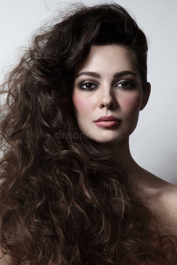 Piękna kobieta z kędzierzawym włosy i dymiącym oko makijażem obrazy royalty free