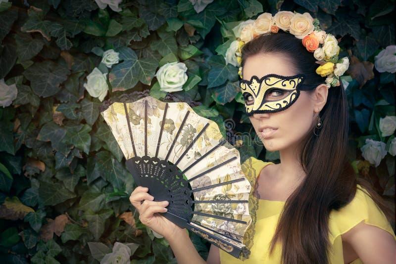 Piękna kobieta z Kwiecistym wiankiem, maską i fan, obrazy royalty free