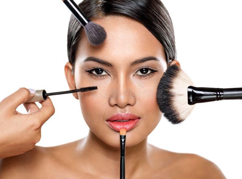 Piękna kobieta z makijażem szczotkuje blisko twarzy zdjęcie stock