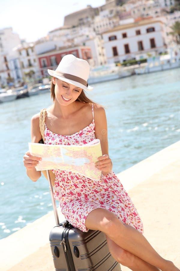 Piękna kobieta z mapy obsiadaniem na walizce zdjęcia royalty free