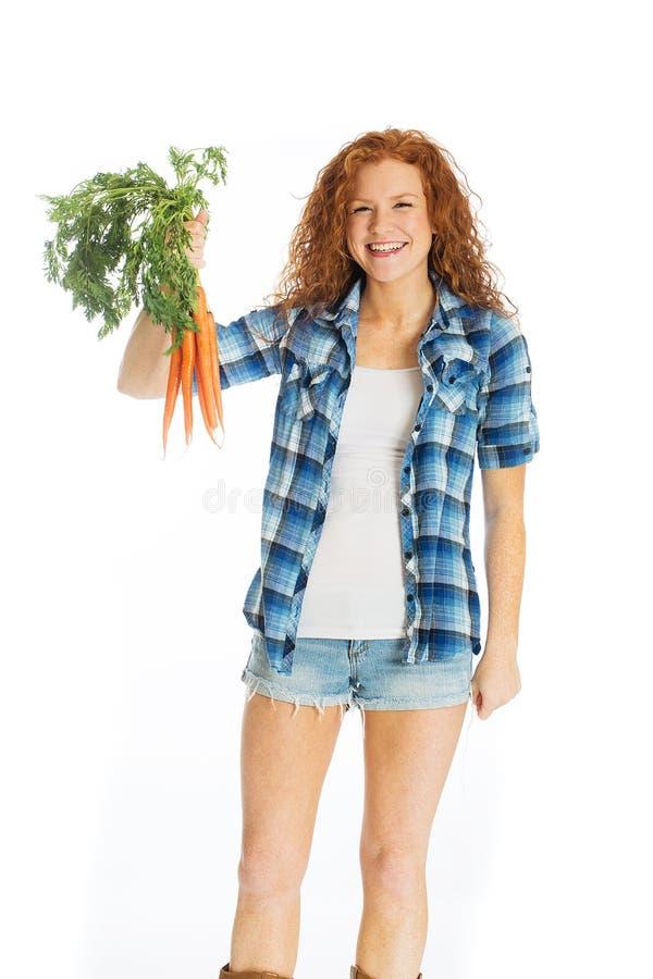 Piękna kobieta z ogrodowymi świeżymi marchewkami fotografia royalty free