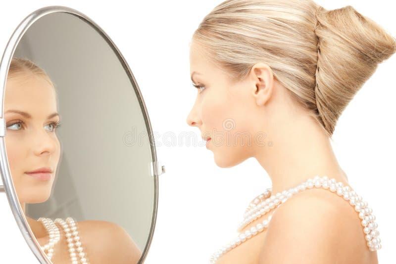 Piękna kobieta z perełkowymi koralikami i lustrem zdjęcia royalty free