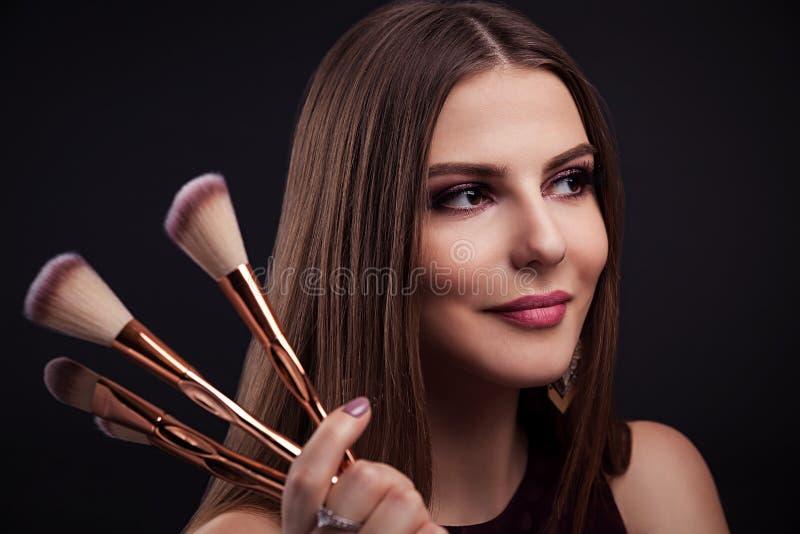 Piękna kobieta z perfect makijażem trzyma makijaży muśnięcia na czarnym tle obrazy stock