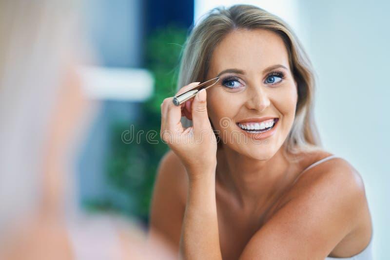 Piękna kobieta z pincetami w łazience zdjęcie stock