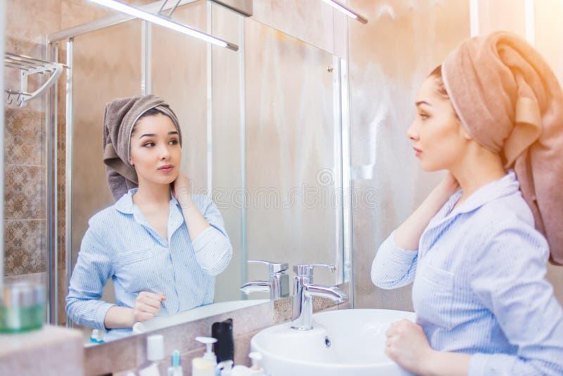 Piękna kobieta z ręcznikiem na jej głowie, patrzeje w lustrze zdjęcie royalty free
