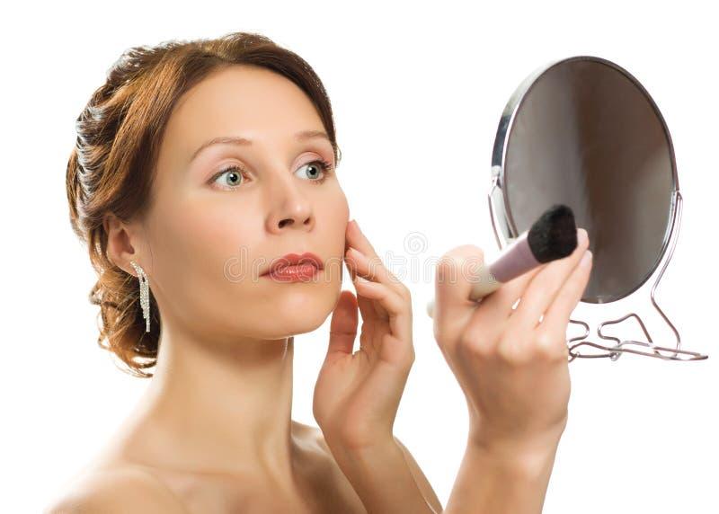 Piękna kobieta z spojrzeniami przy jego twarzą w lustrze obrazy stock