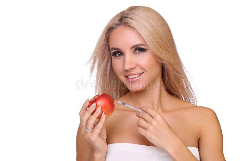 Piękna kobieta z strzykawką czerwona krowiankowa dawka wstrzykuje na jabłku zdjęcie stock