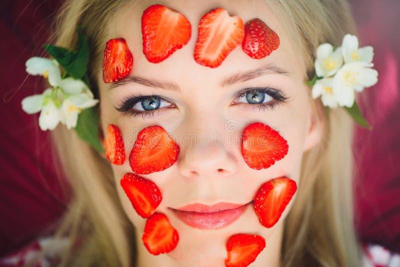 Piękna kobieta z truskawkową maską, zakończenie, twarzowi, naturalni kosmetyki, kłama na naturze w lato ogródzie z jaśminem wewną obraz royalty free