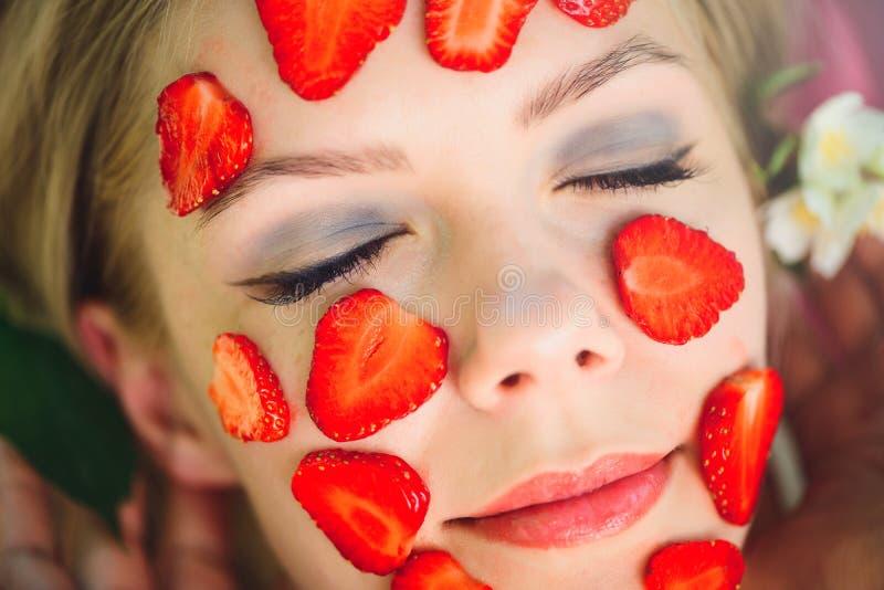 Piękna kobieta z truskawkową maską, zakończenie, twarzowi, naturalni kosmetyki, kłama na naturze w lato ogródzie z jaśminem wewną zdjęcie royalty free