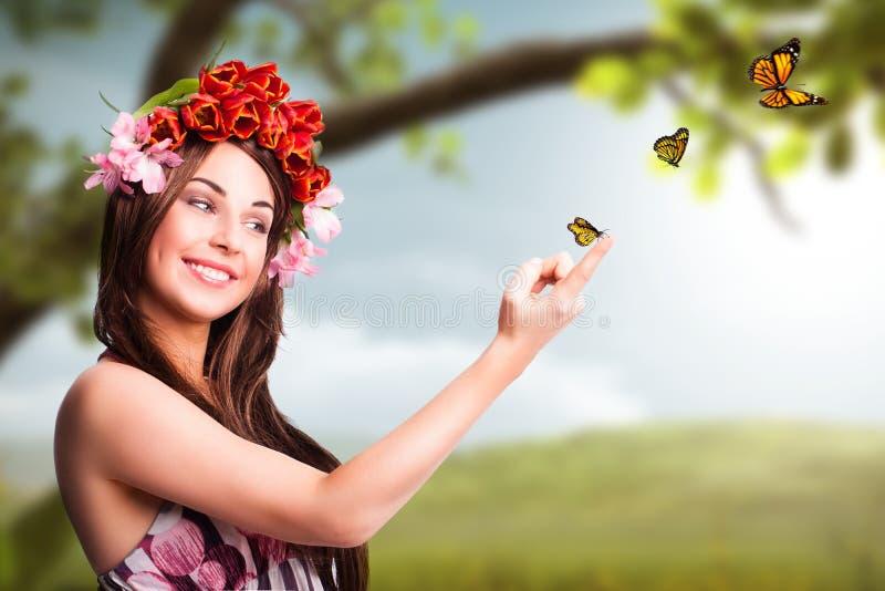 Piękna kobieta z tulipanową włosianą dekoracją i motylami zdjęcie stock