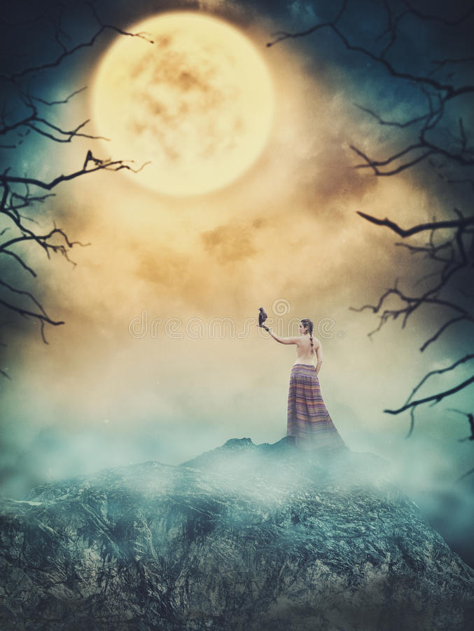 Piękna kobieta z wroną na skale przeciw strasznemu niebu święcący zdjęcia royalty free