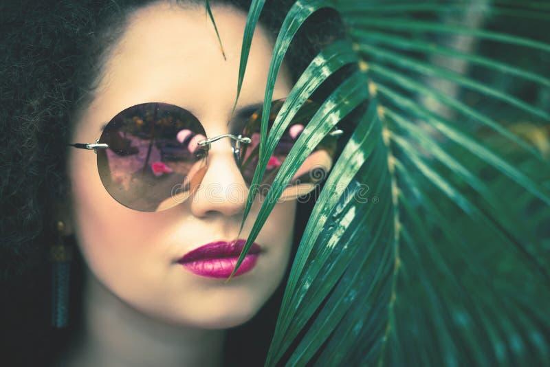 Piękna kobieta z zielonymi palmowymi liśćmi przy ona twarz obraz stock