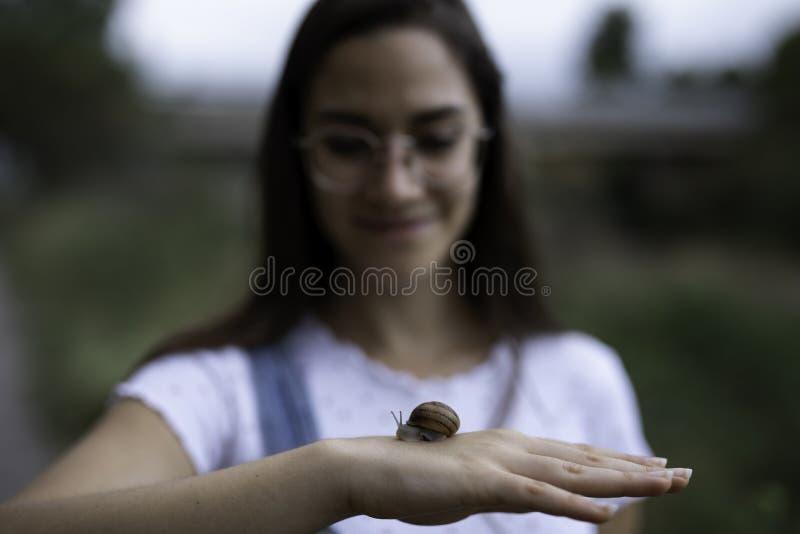 Piękna kobieta zamazująca trzymający ślimaczka w ona outdoors ręki zdjęcie royalty free