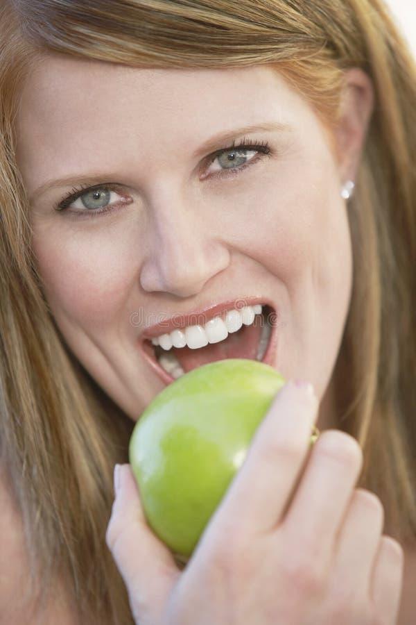Piękna kobiety łasowania zieleń Apple zdjęcie stock