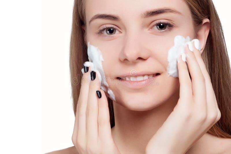 Piękna kobiety cleaning twarz z piankowym traktowania światła tłem fotografia royalty free