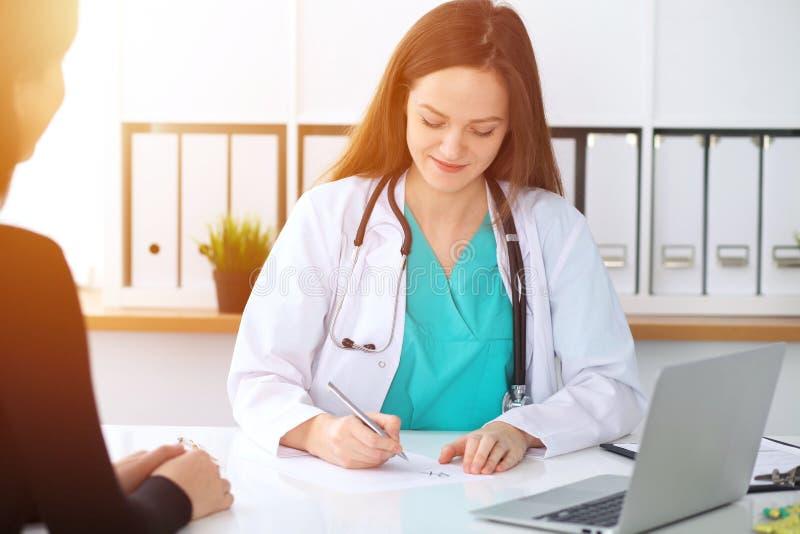 Piękna kobiety lekarka, pacjent ma rozmowę i podczas gdy siedzący przy biurkiem Lekarz pisze recepcie z srebrem obraz stock