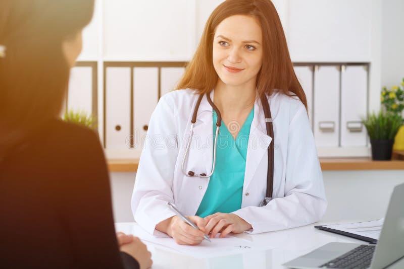 Piękna kobiety lekarka, pacjent ma rozmowę i podczas gdy siedzący przy biurkiem Lekarz pisze recepcie z srebrem obraz royalty free
