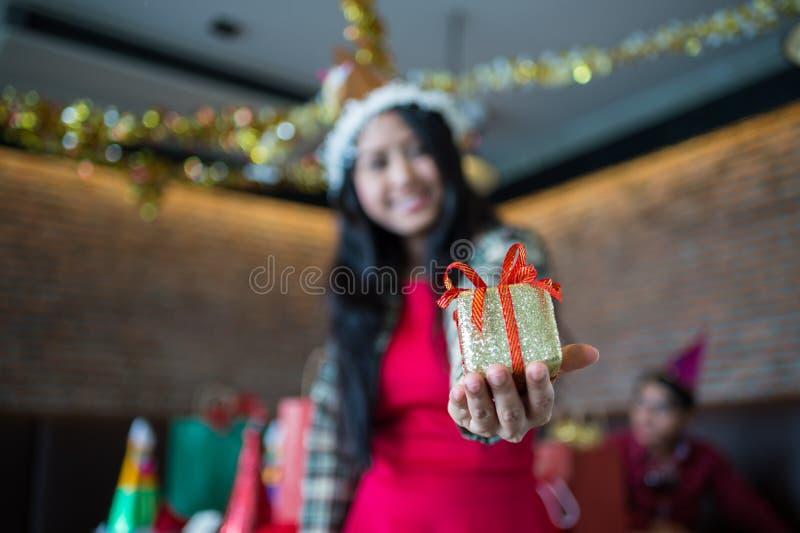 Piękna kobiety odzieży czerwieni suknia i Santa Claus kapelusz pokazuje złotego prezenta pudełko na ręce w restauraci zdjęcia stock