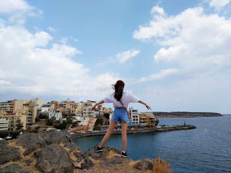 Piękna kobiety pozycja na górze w Agios Nikolaos, Crete, Grecja Odgórny osiągnięcie czu? swobodnie zdjęcie royalty free