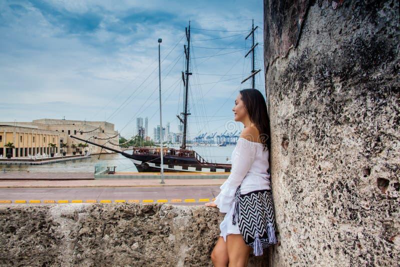 Piękna kobiety pozycja przy ścianami Cartagena De Indias patrzeje zatoka obraz royalty free