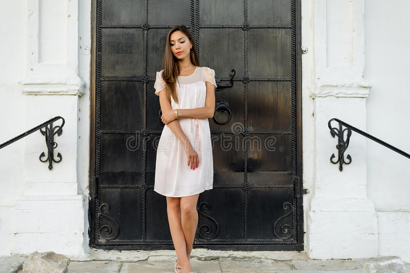 Piękna kobiety pozycja przy czarnym drzwi kasztel, Gocki kościół dziewczyna w różowej sukni odpoczywa, pozujący zakończenie up, fotografia stock