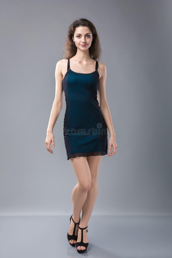 Piękna kobiety pozycja w czarnej sukni nad szarość zdjęcie stock