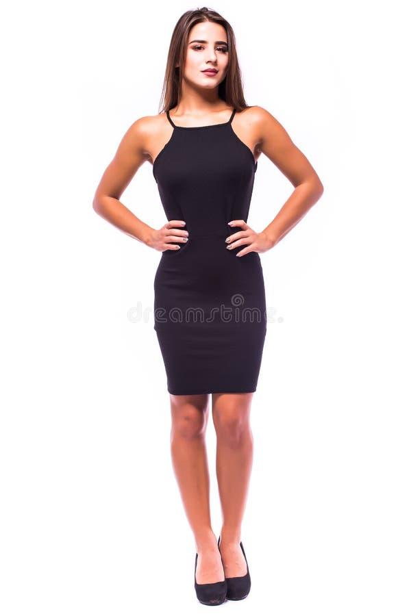 Piękna kobiety pozycja w czarnej sukni nad szarym tłem fotografia royalty free