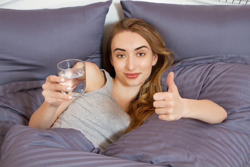 Piękna kobiety woda pitna w łóżku przy ranek kobiety przedstawieniem jak znak Zdrowy stylowy początek dnia pojęcie fotografia royalty free