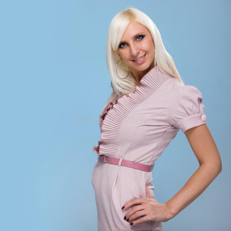 Piękna kokietki młoda kobieta, odizolowywająca na błękicie obraz stock