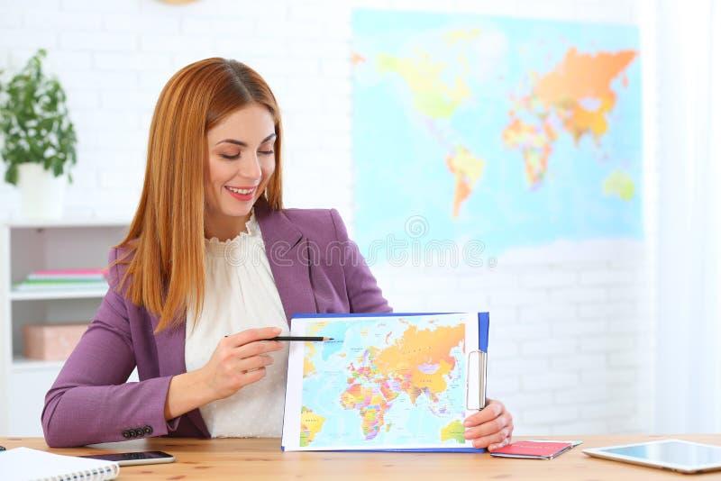 Piękna konsultanta seansu mapa w agencji podróży zdjęcie royalty free
