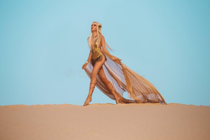 Piękna królowa pustynia w luksusowej złoto sukni obrazy stock