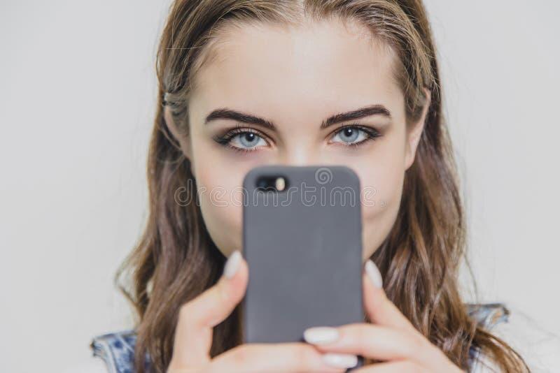 Piękna młoda ładna dziewczyna w niebieskich dżinsów kombinezonach Trzyma telefon w jego rękach patrzeje kamerę W górę dobrego zdjęcia royalty free