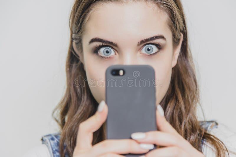 Piękna młoda ładna dziewczyna w niebieskich dżinsów kombinezonach Trzyma telefon w jego rękach patrzeje kamerę W górę dobrego obraz royalty free