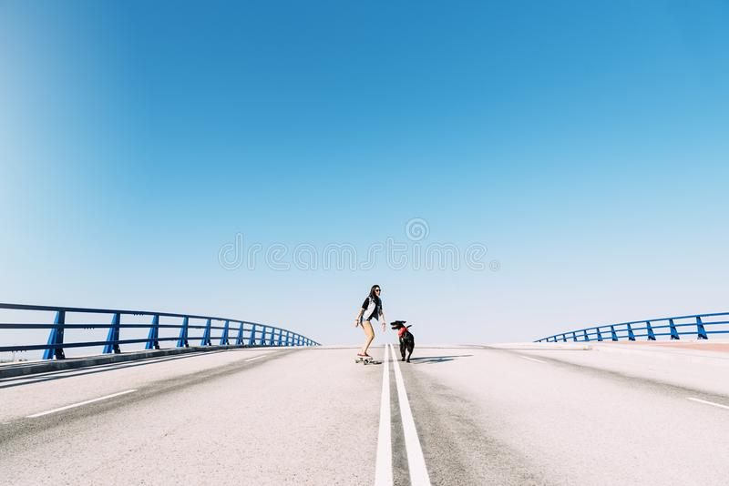 Piękna młoda łyżwiarka bawić się z jej psem obraz stock
