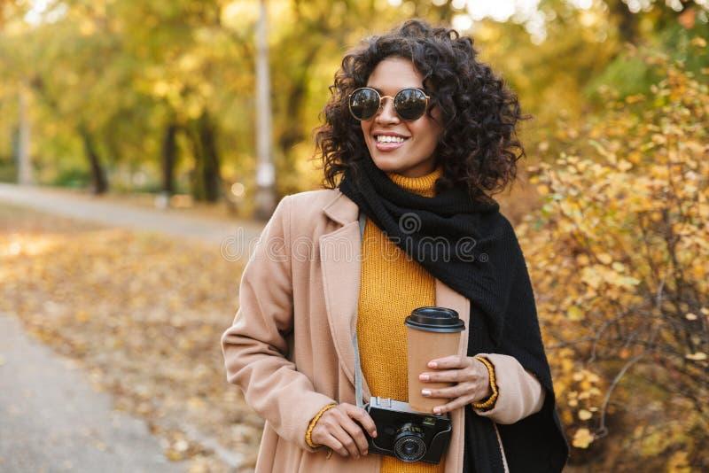 Piękna młoda afrykańska kobieta chodzi outdoors w wiosny parkowej pije kawie obraz stock