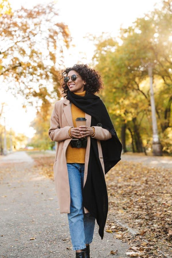 Piękna młoda afrykańska kobieta chodzi outdoors w wiosny parkowej pije kawie obrazy royalty free