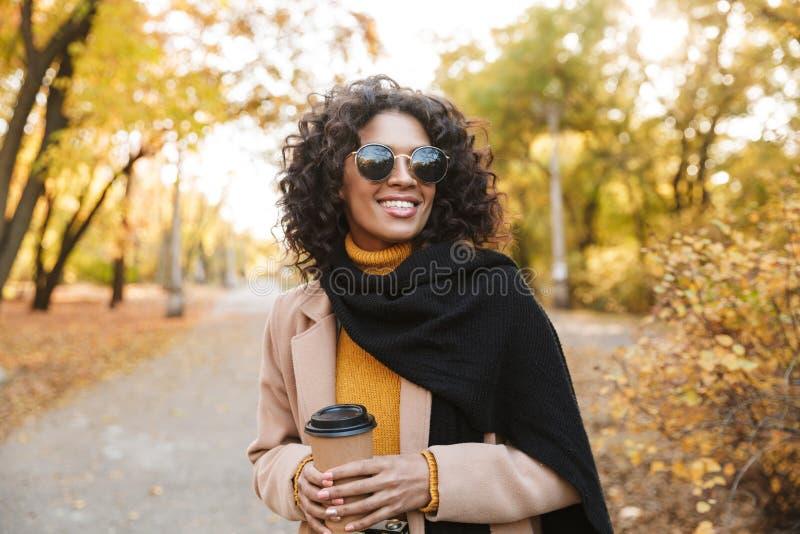 Piękna młoda afrykańska kobieta chodzi outdoors w wiosny parkowej pije kawie zdjęcia stock