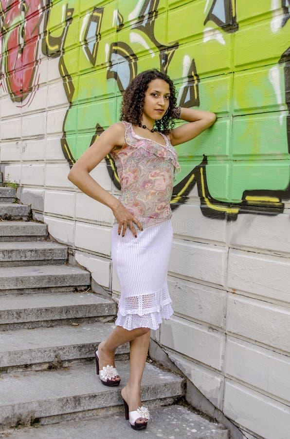 Piękna młoda Afrykańska oliwkowa kobieta w lato sukni w przemysłowym terenie fotografia royalty free